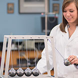 A Teacher Using a Giant Newtons Cradle Giant